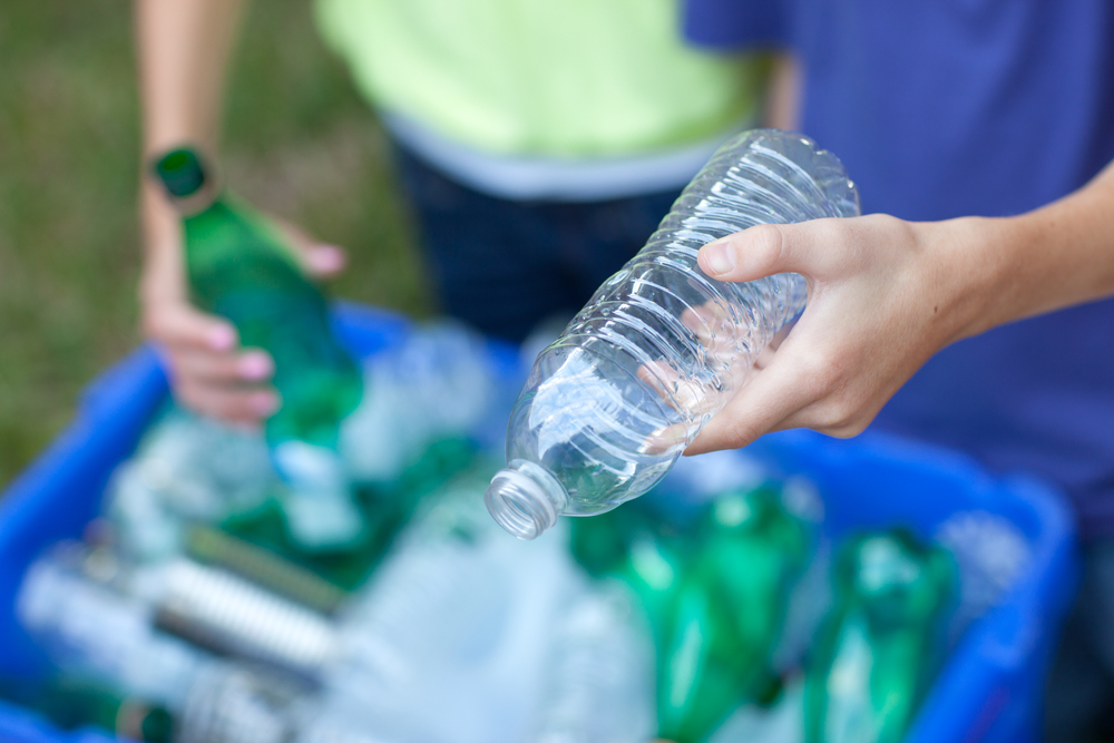 boy recycles plastic bottle for proper waste disposal